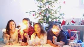 Szczęśliwi młodzi przyjaciele kłamają na dywanika oparzenie błyskają napoju szampana świętują nowego roku w dekorującym pokoju ob zbiory