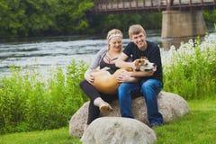 Szczęśliwi młodzi właściciele trzyma psa i muska je Fotografia Stock