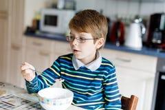 Szczęśliwi mali blondyny żartują chłopiec łasowania zboża dla śniadania lub lunchu Dla dzieci zdrowy łasowanie Obrazy Royalty Free