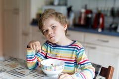 Szczęśliwi mali blondyny żartują chłopiec łasowania zboża dla śniadania lub lunchu Dla dzieci zdrowy łasowanie Zdjęcie Royalty Free