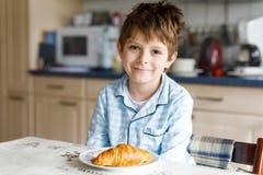 Szczęśliwi mali blondyny żartują chłopiec je świeżego croissant dla śniadania lub lunchu Dla dzieci zdrowy łasowanie Obraz Stock