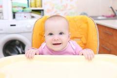 Szczęśliwi mali 7 miesięcy dziewczynki na dziecka krześle Fotografia Stock