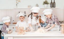 Szczęśliwi mali szefowie kuchni przygotowywa ciasto w kuchni obraz royalty free