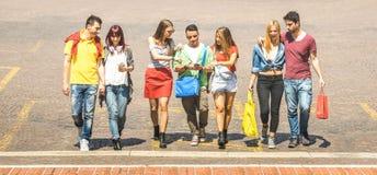 Szczęśliwi najlepszy przyjaciele chodzi i opowiada w centrum miasta - Turystyczni faceci i dziewczyny millennial mieć zabawę woko obraz royalty free