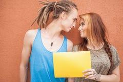 Szczęśliwi nastolatkowie dobierają się patrzeć i trzymać ramowy przy czerwonym tłem Fotografia Stock