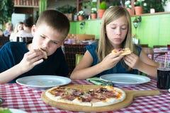 Szczęśliwi nastolatkowie je pizzę w kawiarni Przyjaciele lub rodzeństwa ma zabawę w restauracji obraz stock