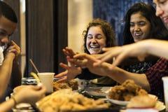 Szczęśliwi nastolatkowie wpólnie je fasta food szybkiego żarcia otyłość i niezdrowego posiłku pojęcie obraz stock