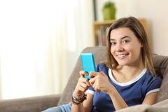 Szczęśliwi nastoletni chwyty mądrze telefon patrzeje ciebie obrazy royalty free