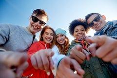 Szczęśliwi nastoletni przyjaciele wskazuje palce na ulicie obrazy stock