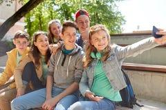 Szczęśliwi nastoletni ucznie bierze selfie smartphone zdjęcia stock