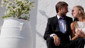 Szczęśliwi nowożeńcy siedzi blisko ich hotelu na ich dniu ślubu zbiory