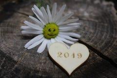 Szczęśliwi nowy rok powitania z roześmianym kwiatem i drewnianym sercem fotografia stock