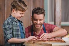 Szczęśliwi ojca i syna kulinarni mięśni paszteciki wpólnie Obraz Stock