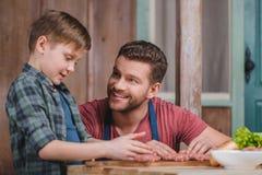 Szczęśliwi ojca i syna kulinarni mięśni paszteciki wpólnie Zdjęcia Stock