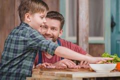 Szczęśliwi ojca i syna kulinarni mięśni paszteciki wpólnie Obraz Royalty Free