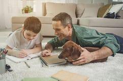 Szczęśliwi ojca nauczania chłopiec maths w domu Zdjęcia Royalty Free