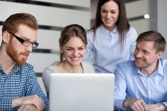 Szczęśliwi ono uśmiecha się biurowi pracownicy patrzeje laptop zespalają się mieć zabawę obrazy stock