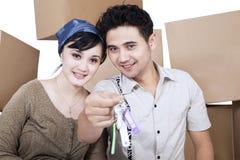 Szczęśliwi para chwyta klucze przy nowym domem Obrazy Stock