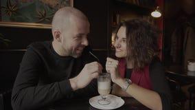 Szczęśliwi para nowożeńcy siedzi w kawiarni i pije latte od jeden filiżanki zbiory