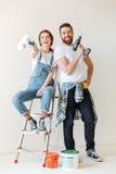 Szczęśliwi para seansu narzędzia dla naprawy podczas gdy stojący blisko drabiny Zdjęcia Stock