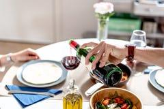 Szczęśliwi potomstwa dobierają się łasowanie i pić w domu wino Zdjęcia Stock