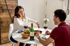 Szczęśliwi potomstwa dobierają się łasowanie i pić w domu wino Zdjęcia Royalty Free