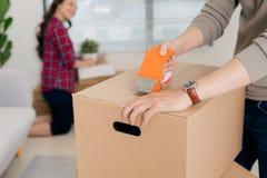 Szczęśliwi potomstwa dobierają się chodzenie w nowego mieszkanie z pakować boxe obraz stock
