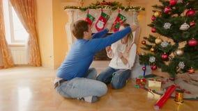 Szczęśliwi potomstwa dobierają się dekorować choinki i rzucać świecidełko przy each inny zdjęcie wideo