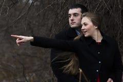 Szczęśliwi potomstwa dobierają się mężczyzna patrzeje dokąd kobieta wskazuje w parku Obraz Stock