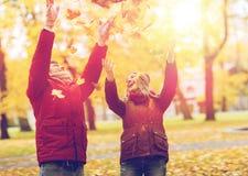 Szczęśliwi potomstwa dobierają się miotanie jesieni liście w parku Obrazy Stock