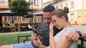 Szczęśliwi potomstwa dobierają się obsiadanie na ławce i używać mądrze telefon Kobiety i mężczyzna dopatrywania wideo, fotografie zbiory wideo