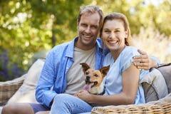 Szczęśliwi potomstwa dobierają się obsiadanie z ich zwierzę domowe psem w ogródzie obraz stock