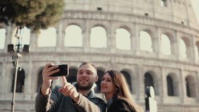 Szczęśliwi potomstwa dobierają się używać smartphone dla brać selfie fotografię blisko Colosseum w Rzym, Włochy Mężczyzna i kobie zbiory