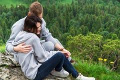 Szczęśliwi potomstwa dobierają się w miłości siedzi na górze, przytuleniu i lo, Obrazy Royalty Free