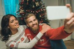 szczęśliwi potomstwa dobierają się w zima pulowerach bierze selfie fotografia stock