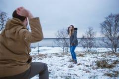Szczęśliwi potomstwa dobierają się w zimie odziewają bawić się snowballs outdoors Zdjęcie Royalty Free