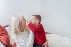 Szczęśliwi potomstwa macierzyści bawić się jej małego syna w domu obraz royalty free