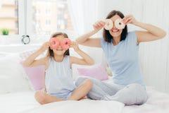Szczęśliwi potomstwa matka i córka zabawę wpólnie, trzymają smakowitych słodkich pączków oczy blisko, siedzą krzyżować nogi na wy obraz stock