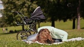Szczęśliwi potomstwa matkują sztuki z dzieckiem na gazonie, całuje jej syna zdjęcie wideo