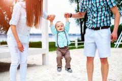 Szczęśliwi potomstwa wychowywają z mały syna bawić się plenerowy w parku fotografia stock