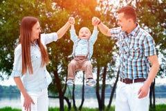 Szczęśliwi potomstwa wychowywają z mały syna bawić się plenerowy w parku zdjęcie royalty free