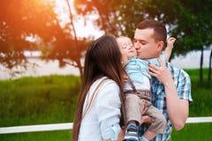 Szczęśliwi potomstwa wychowywają z mały syna bawić się plenerowy w parku zdjęcie stock