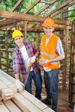 Szczęśliwi pracownicy budowlani Pracuje Przy miejscem Zdjęcie Stock