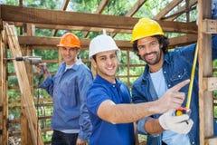 Szczęśliwi pracownicy budowlani Pracuje W Drewnianej kabinie Obrazy Royalty Free