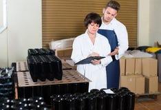 Szczęśliwi pracownicy liczy liczbę wino butelki Fotografia Stock