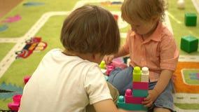 Szczęśliwi preschool berbecie bawić się z wielo- coloured blokami przy salowym boiskiem Edukacja w przedszkolu zbiory wideo