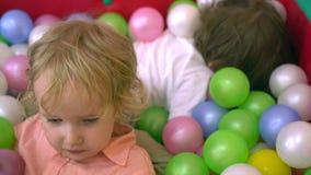 Szczęśliwi preschool dzieciaki ma zabawę i bawić się w wielo- coloured balowym basenie dzieciniec zdjęcie wideo