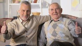 Szczęśliwi przechodzić na emeryturę mężczyźni pokazuje aprobaty i patrzeje in camera, zdrowi emeryci zbiory