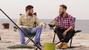 Szczęśliwi przyjaciele łowi piwo na molu i pije zbiory