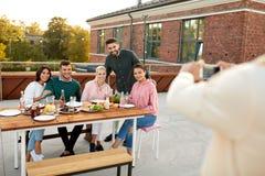 Szczęśliwi przyjaciele fotografuje przy dachu przyjęciem obrazy royalty free